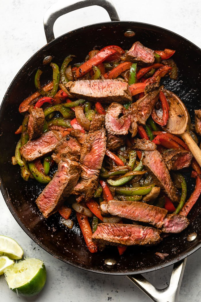 Large pan filled with cooked fajita veggies and sliced steak. Next to the pan is sliced limes.