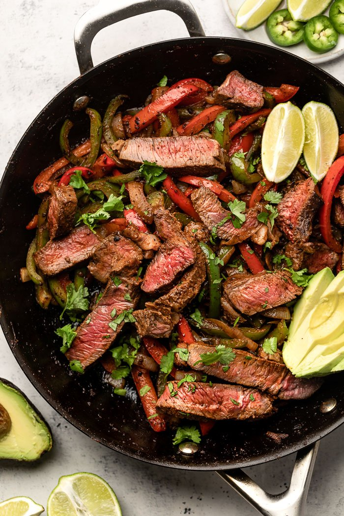 Large pan filled with healthy steak fajitas. In the pan is also some sliced avocado and lime wedges.