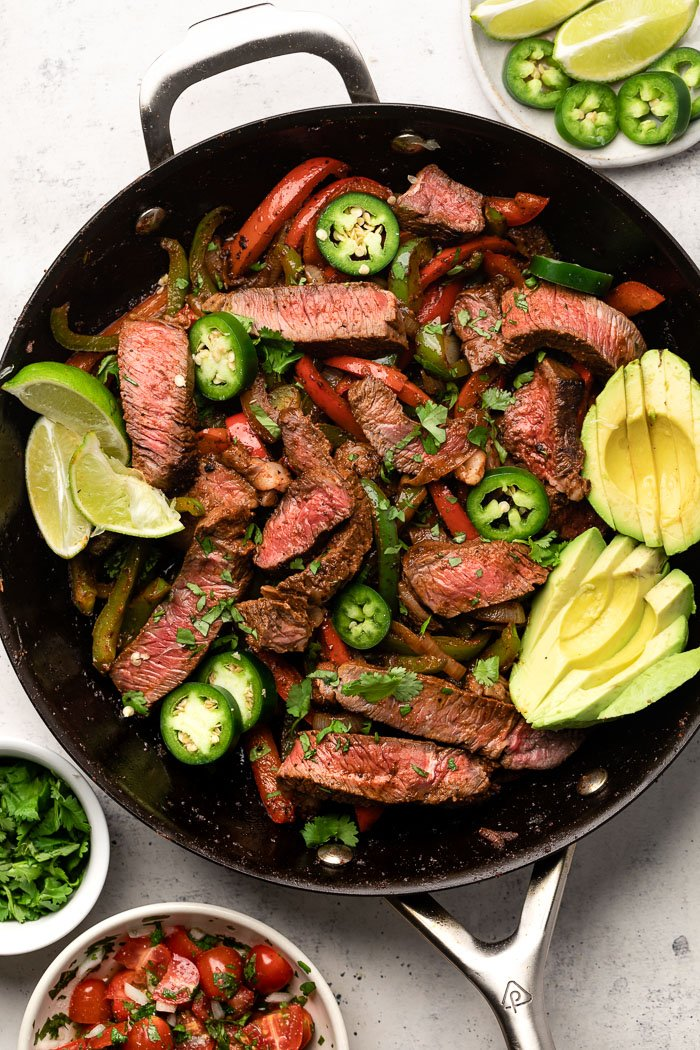 Easy steak fajitas in a large pan garnished with sliced avocado, sliced jalapeños, and lime wedges. Around it is a bowl of salsa, bowl of cilantro, and a platte with jalapeños and limes.