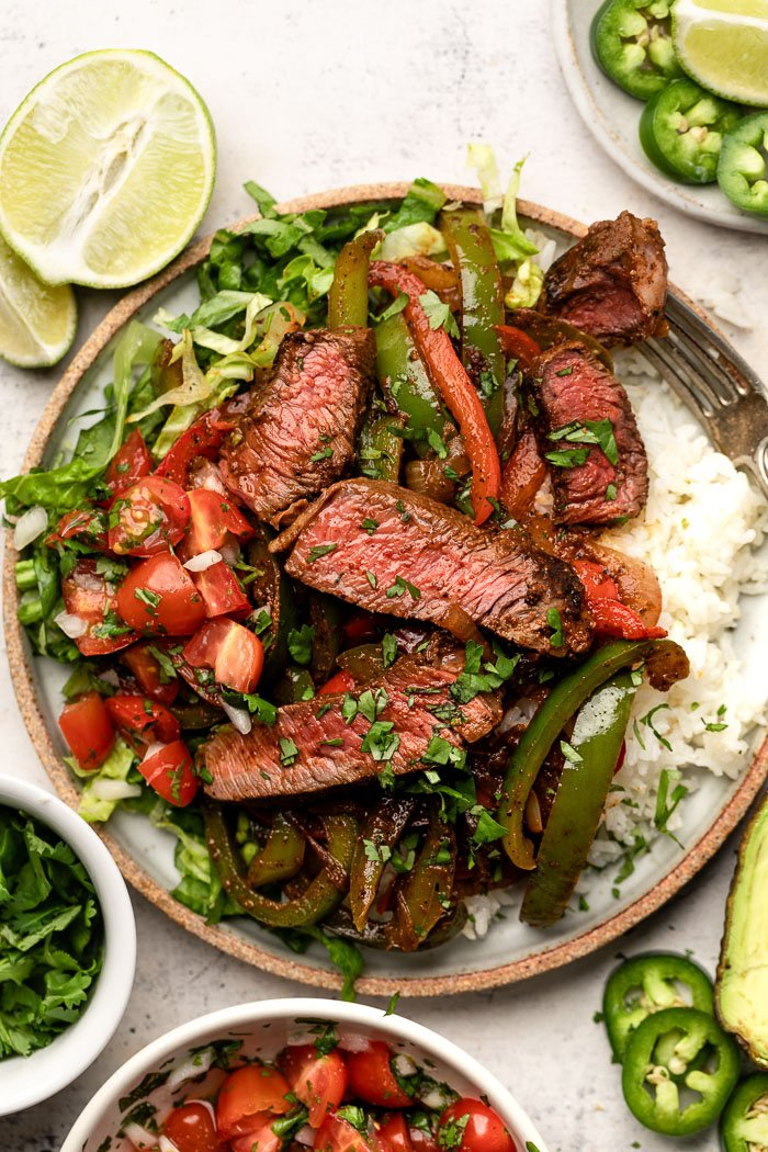 Large plate loaded with white rice, steak fajitas, chopped lettuce and tomatoes, and herbs. Around it is a bowl of diced tomatoes, bowl of cilantro, lime wedges, and a plate of sliced jalapeños.