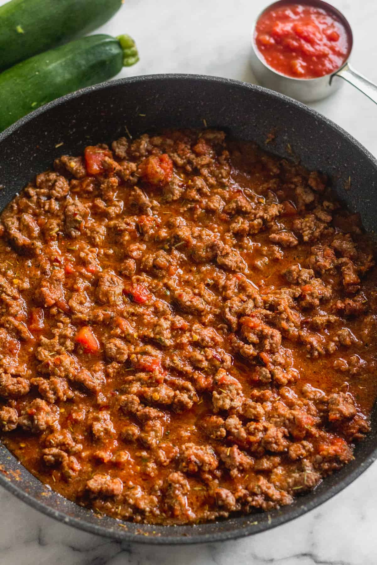 Pan filled with sautéed Italian ground beef, crushed tomatoes, and tomato sauce