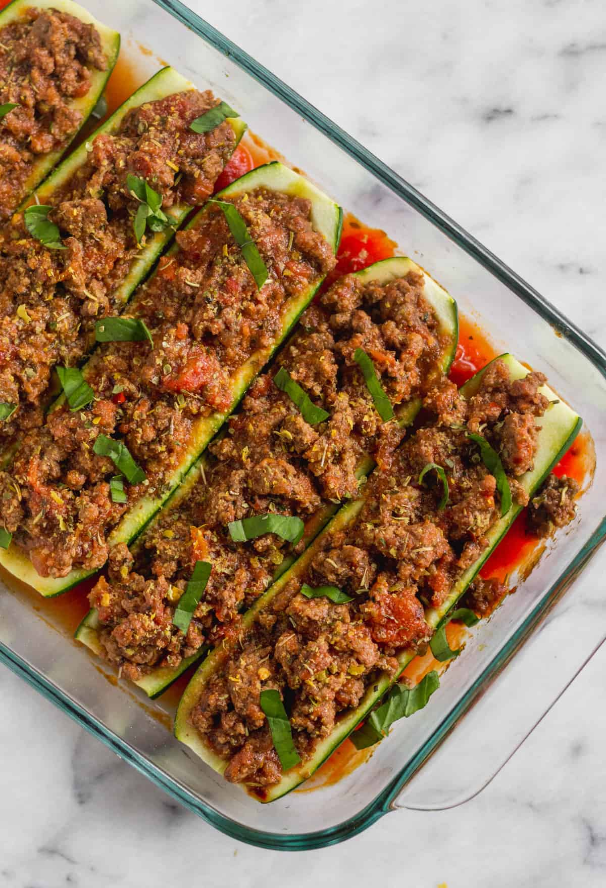 Pan filled with zucchini boats stuffed with Italian seasoned beef and tomato sauce topped with fresh basil