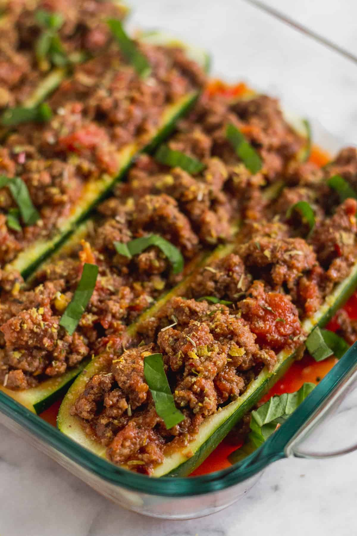 Glass baking dish filled with Italian beef stuffed zucchini boats topped with fresh basil