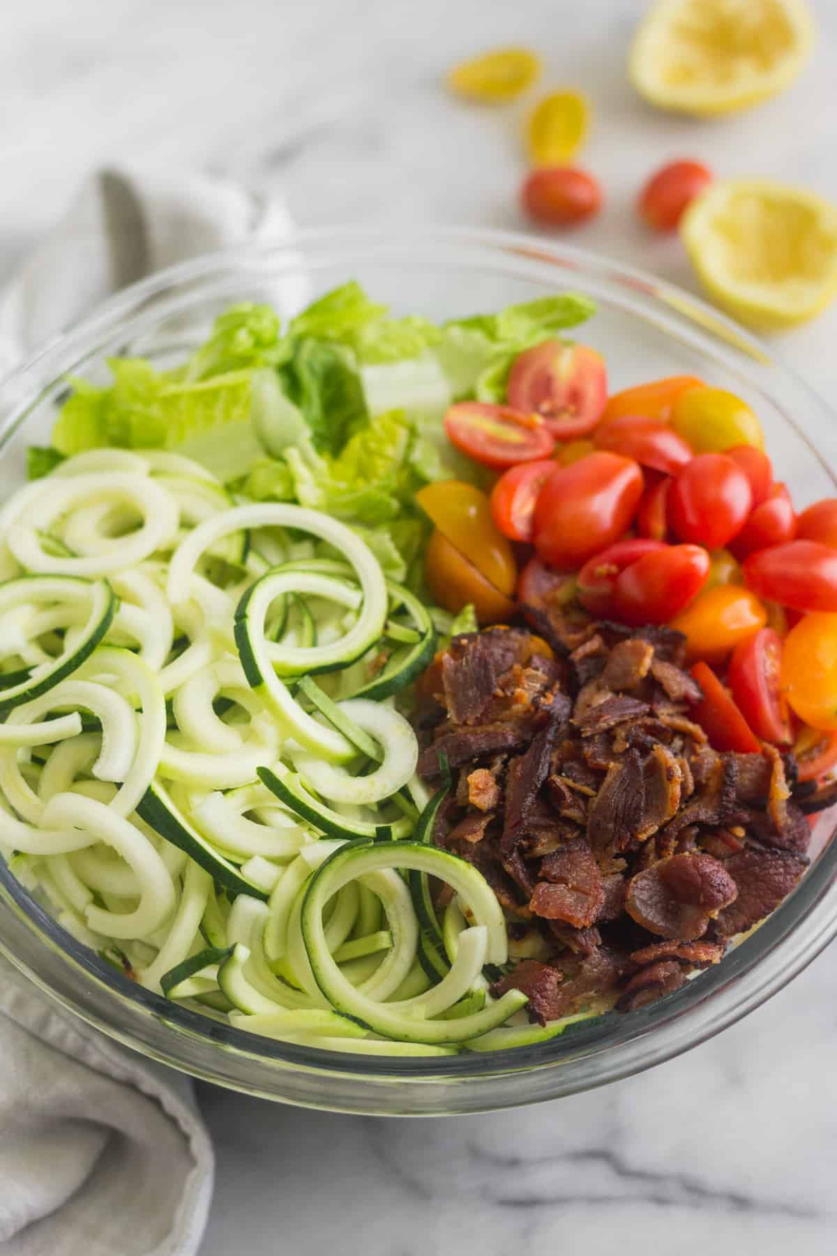 Large glass bowl with zucchini noodles, chopped romaine, cherry tomatoes, and bacon for BLT Zucchini Noodle Pasta Salad