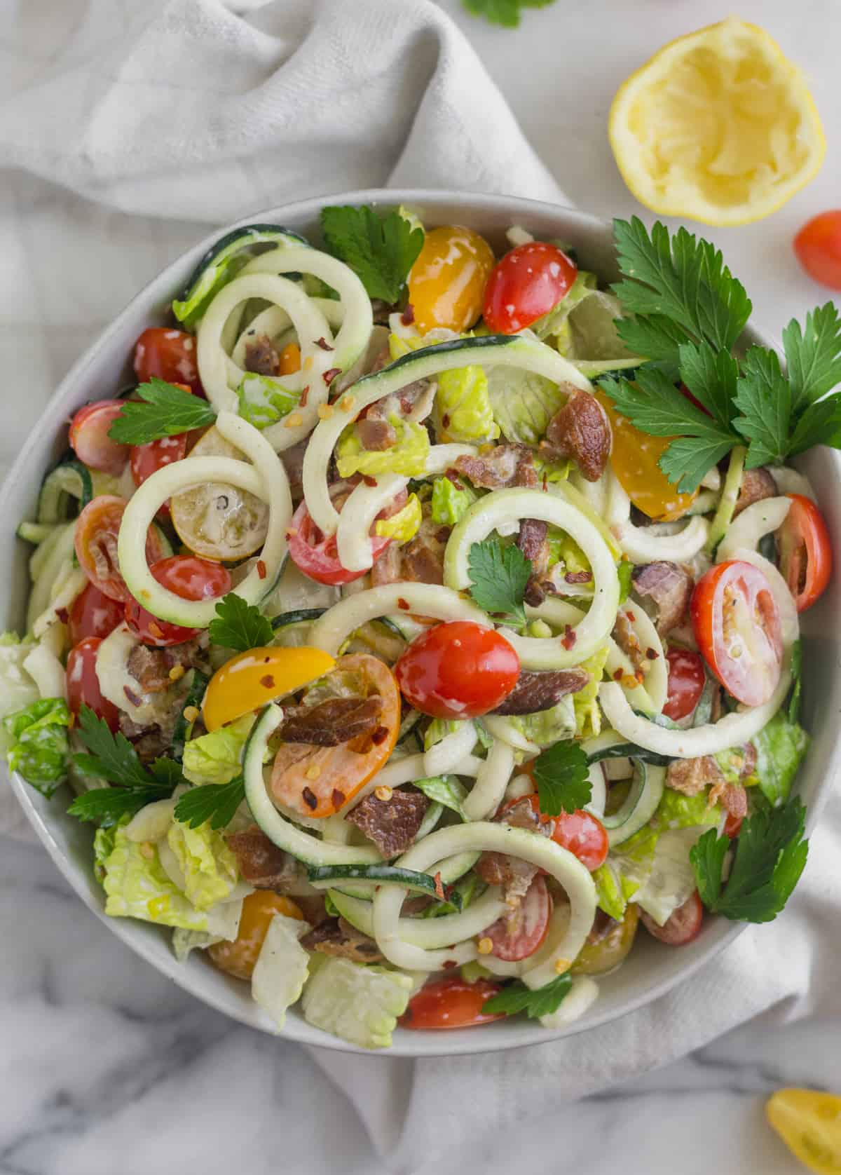 Overhead shot of Large glass bowl with zucchini noodles, chopped romaine, cherry tomatoes, and bacon for BLT Zucchini Noodle Pasta Salad in a white bowl on a white counter