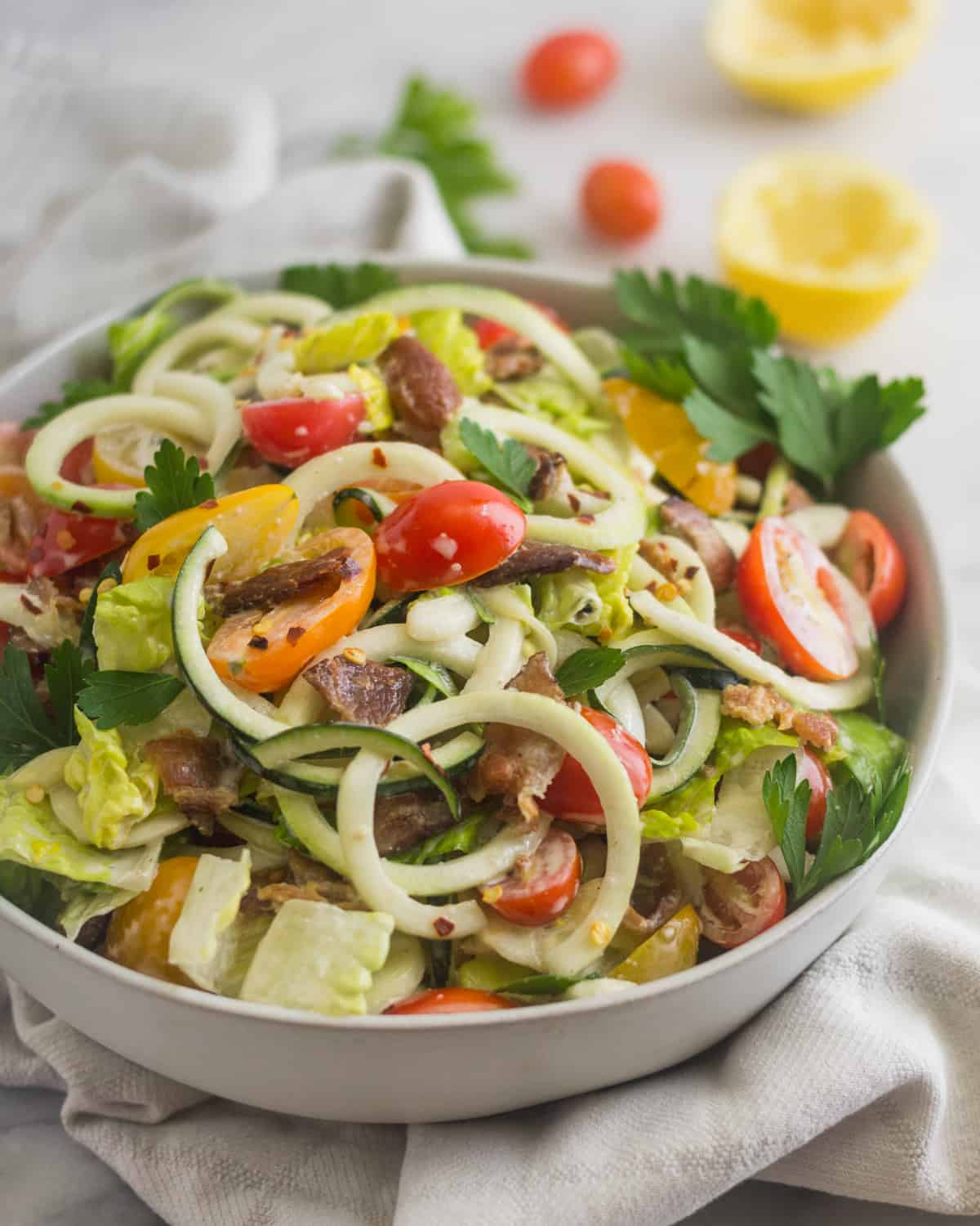 Large white bowl of BLT Zucchini Noodle Pasta Salad with half a lemon and cherry tomatoes behind it