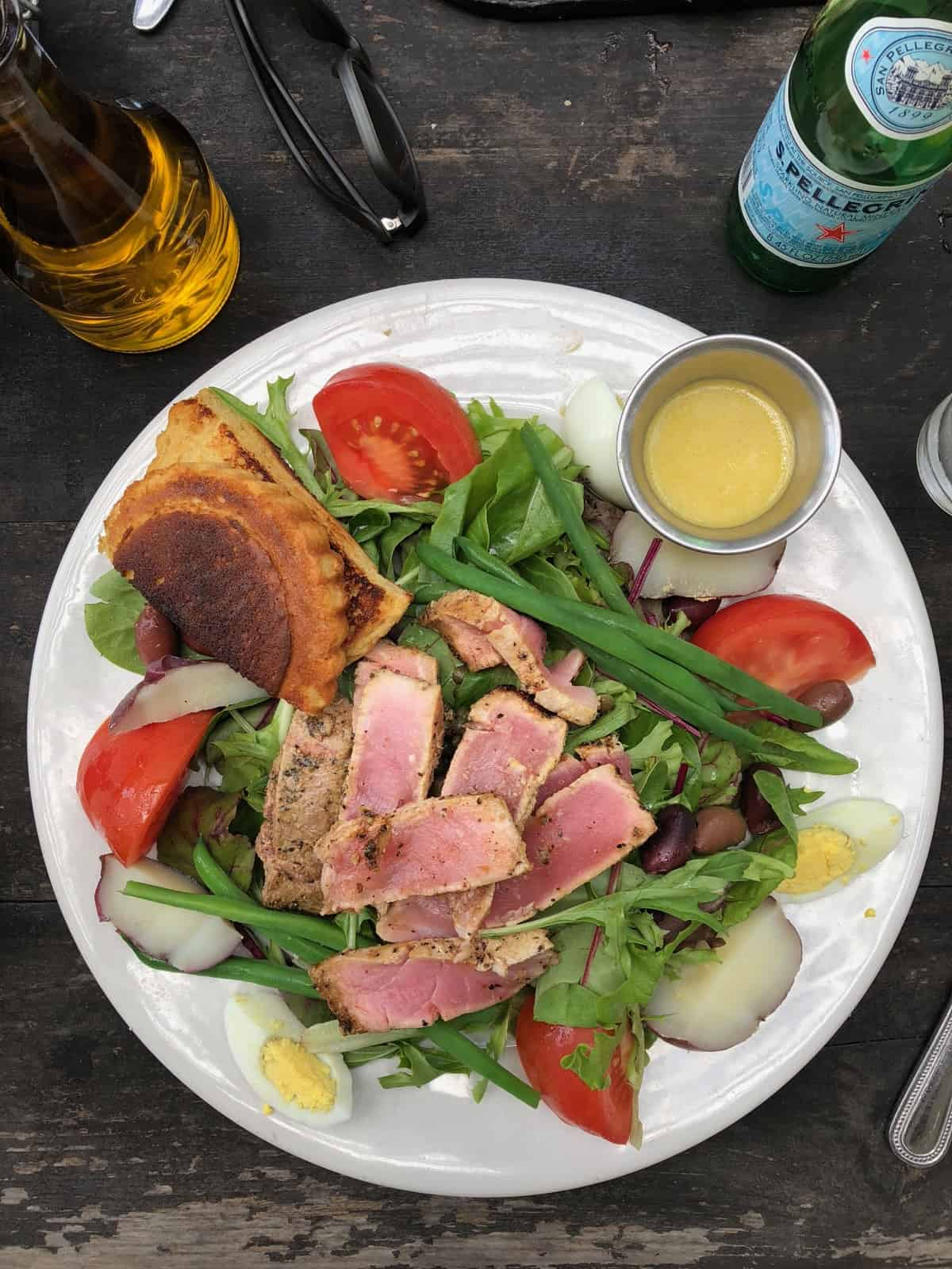 Tuna nicoise salad with gluten free bread and dressing on the side