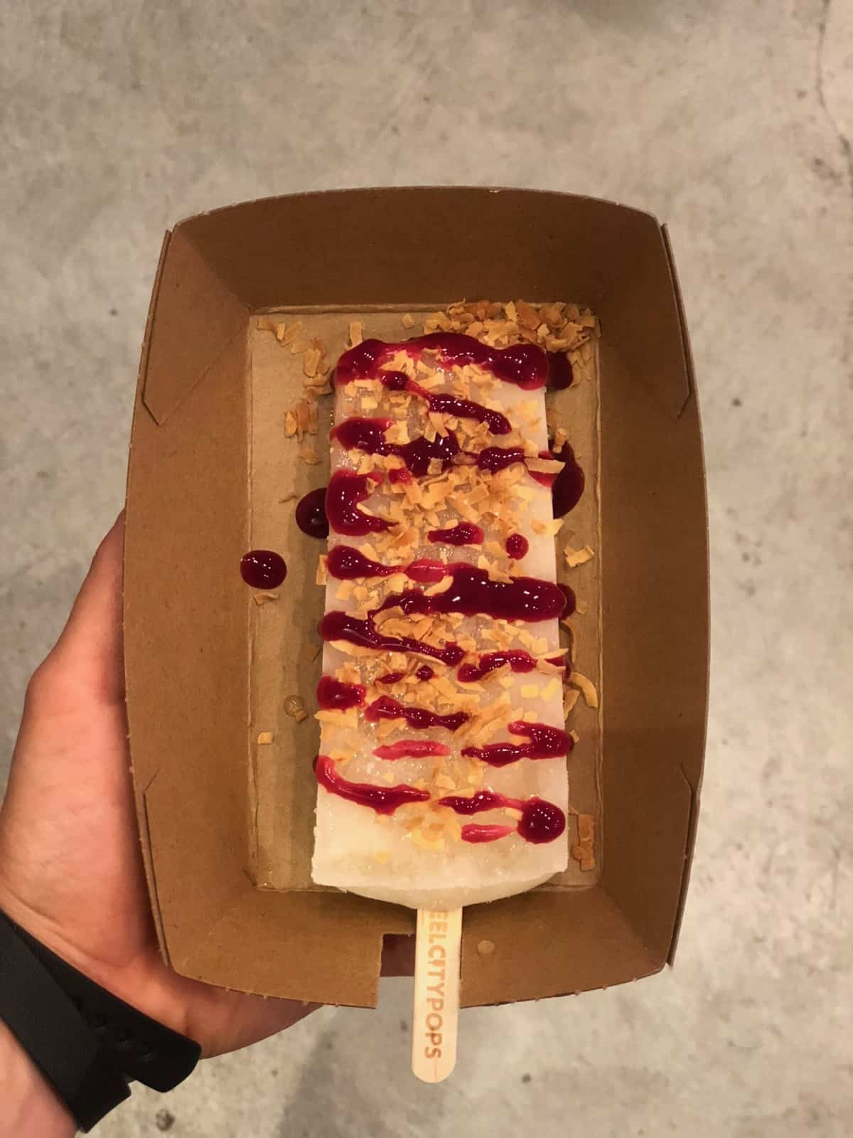 Steel City Popsicle covered with raspberry spread and toasted coconut