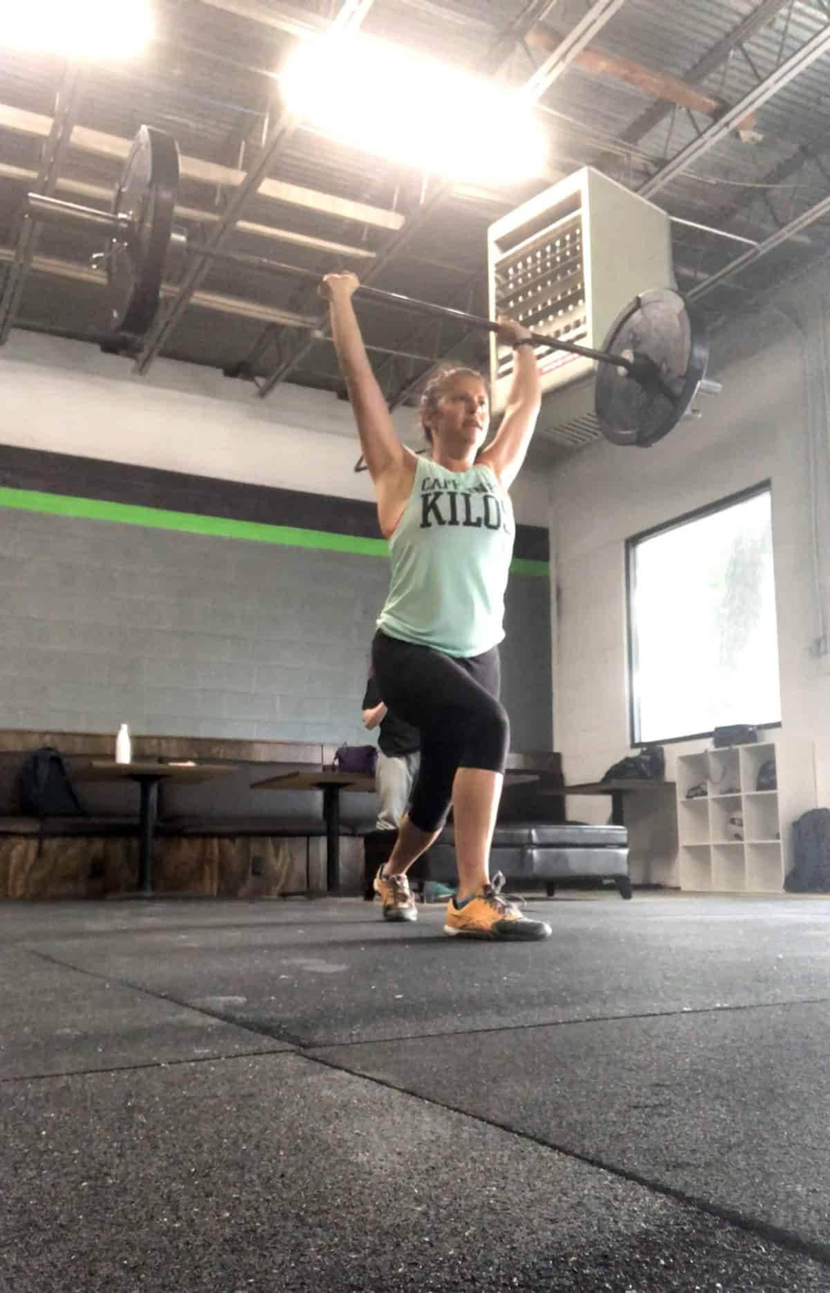 Girl in the catch position of a split jerk with a barbell over her head