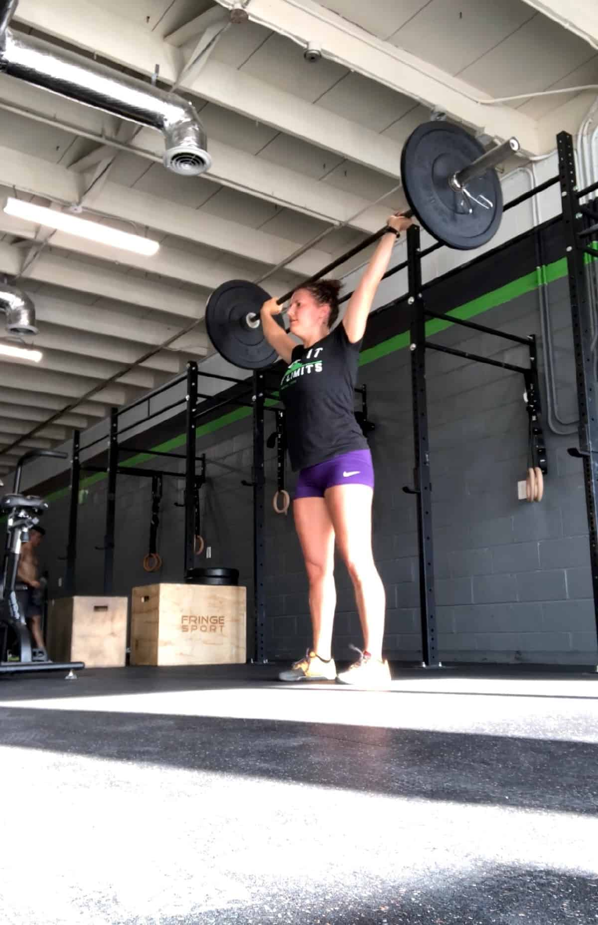 Girl holding a barbell over her head after doing a snatch