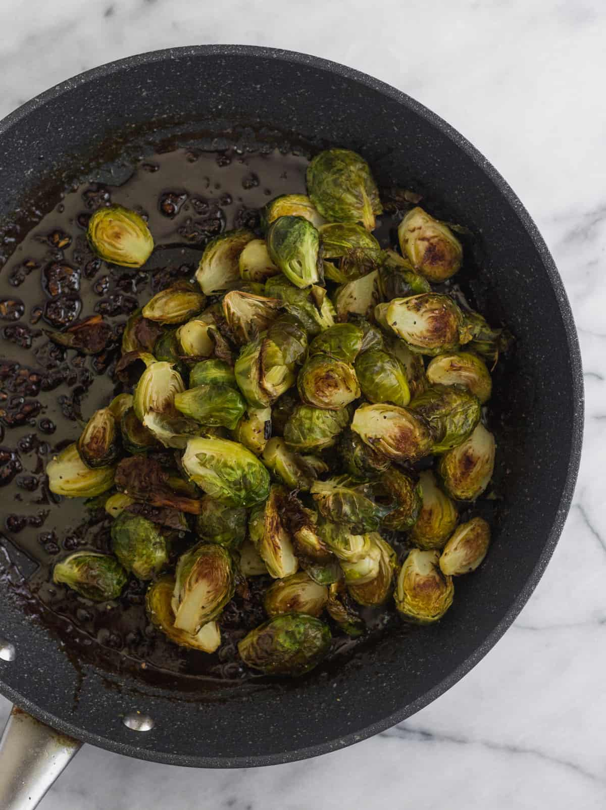 Saute pan filled with miso sauce and roasted brussels sprouts
