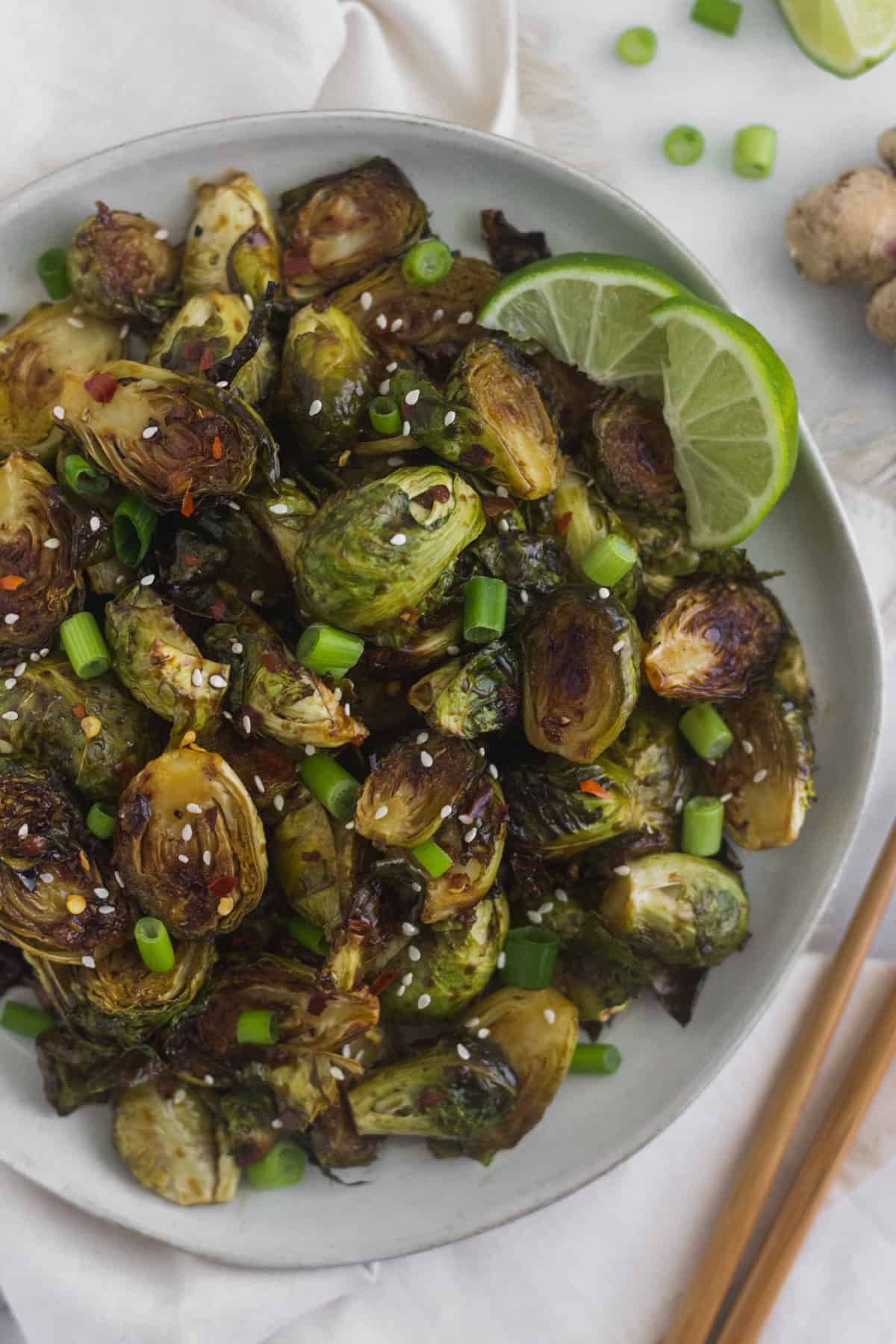 Plate of miso glazed brussels sprouts garnished with green onions, sesame seeds, and lime wedges