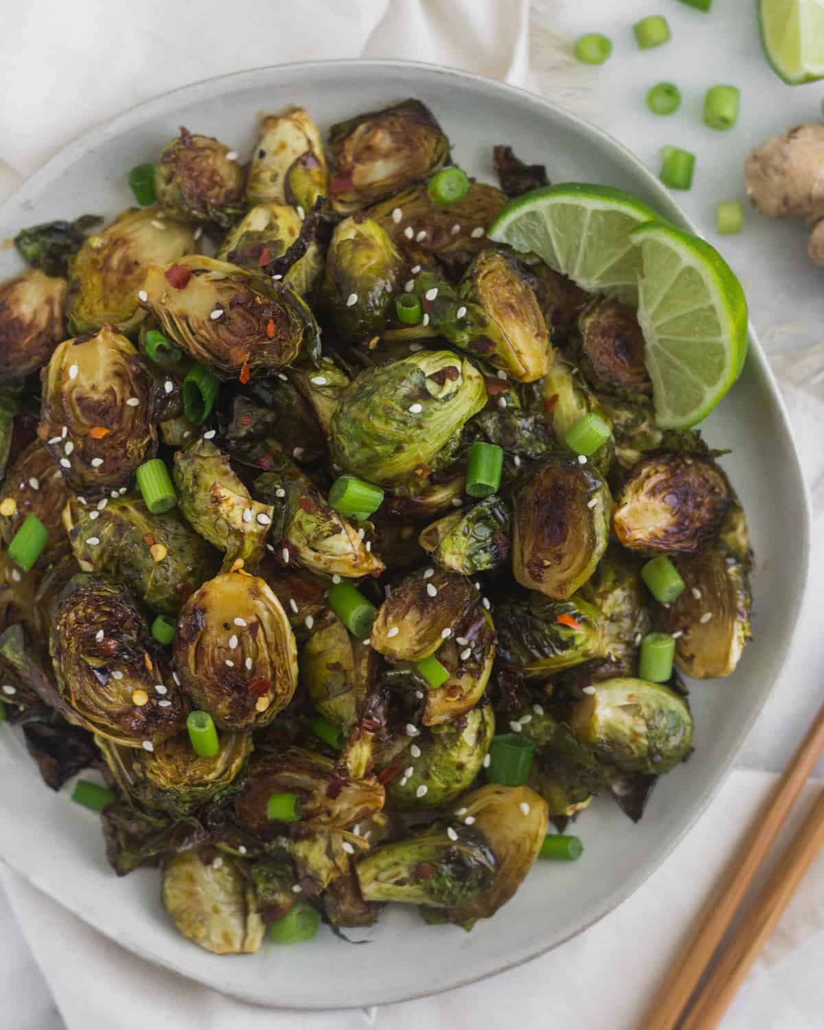Plate of miso glazed brussels sprouts garnished with sesame seeds, green onion, and lime wedges surrounded by chopsticks and more green onions and limes