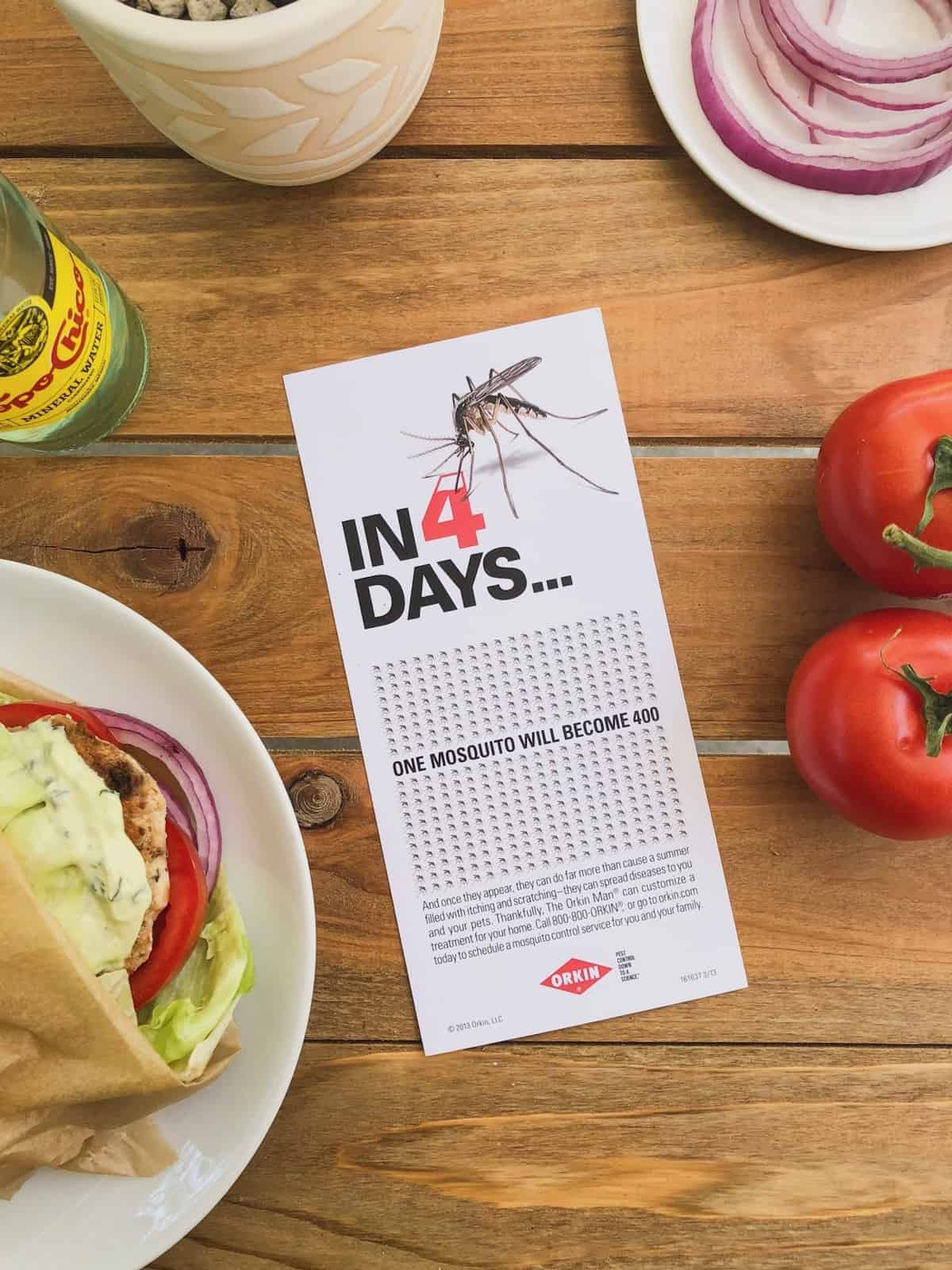 Brochure on a table talking about mosquito treatment surrounded by a Sun Dried Tomato Chicken Burger, tomatoes, cut up red onions, and a topo chico