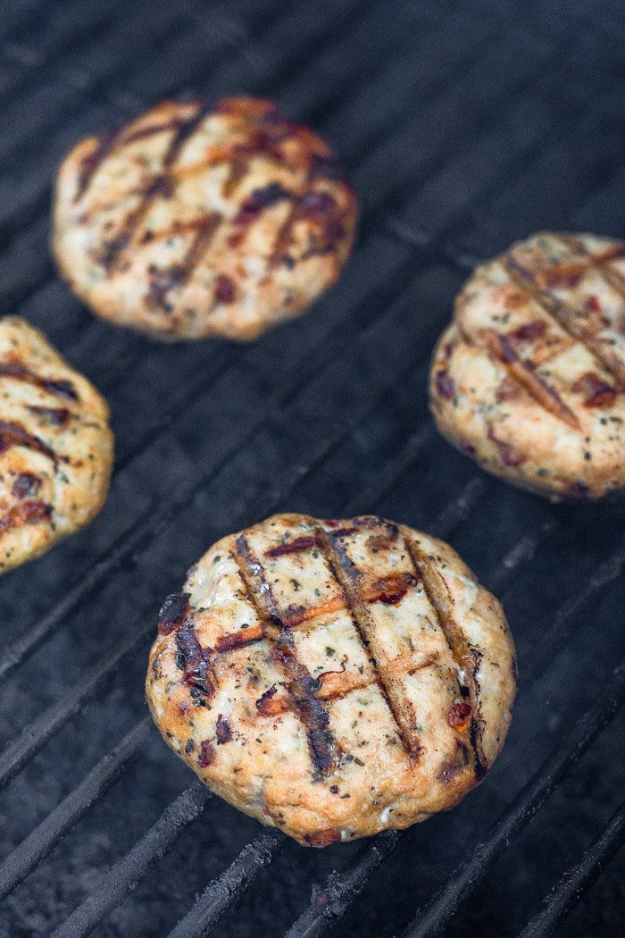 Grilled chicken burgers on a grill.