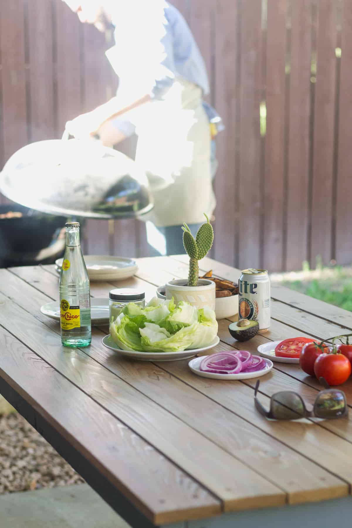 Outdoor wooden table full of toppings for burgers with a man grilling on a charcoal grill behind it