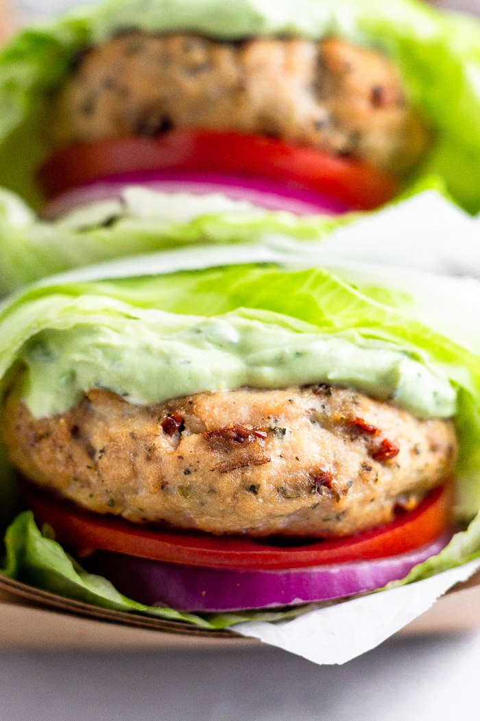 Basket of two grilled chicken burgers with tomato, onion, and basil aioli in lettuce wraps in a basket.