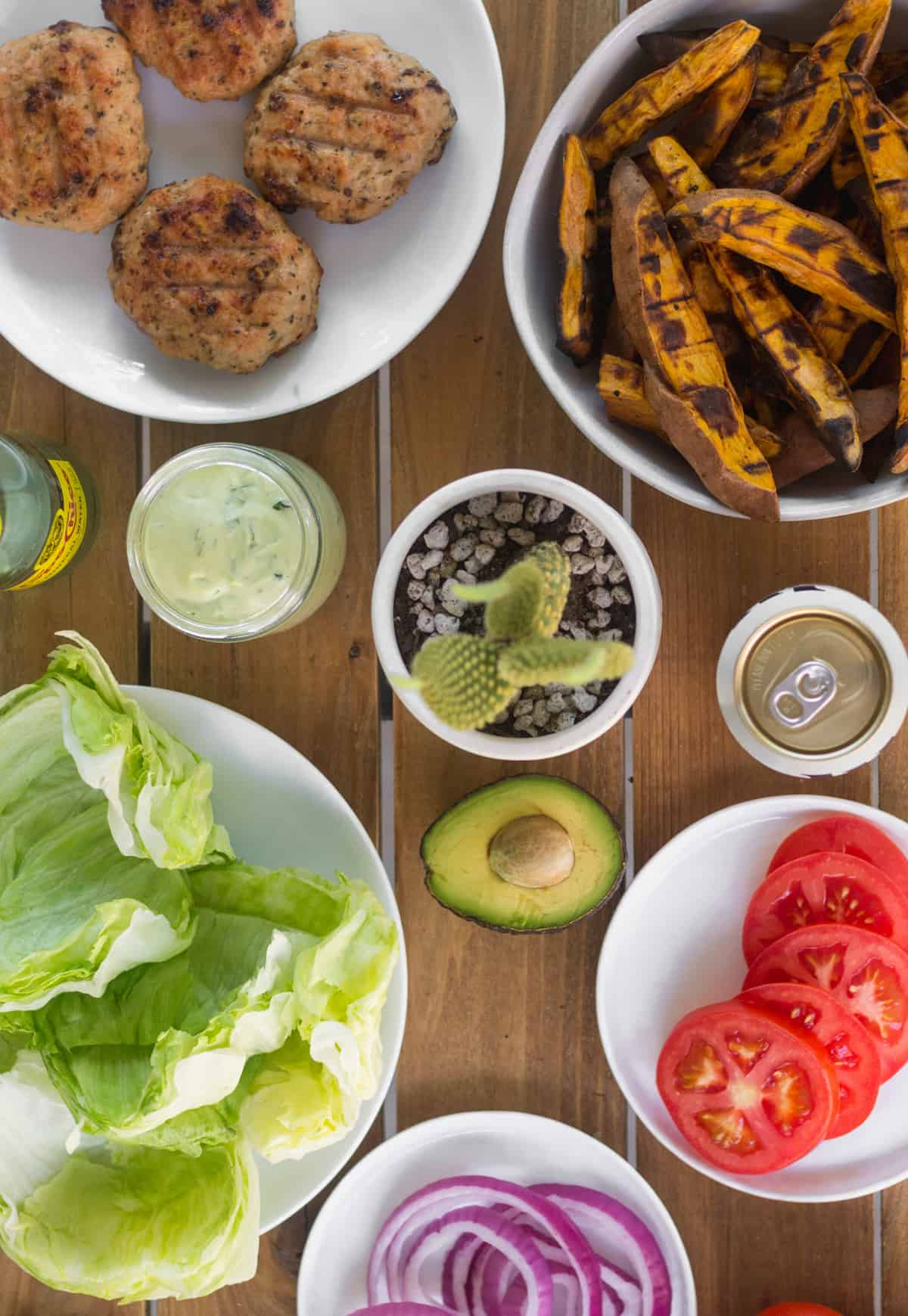 Table spread of a bunch of burger topping and side dishes - lettuce, tomato, red onion, avocado, aioli, sweet potato fries, beer, and sparkling water