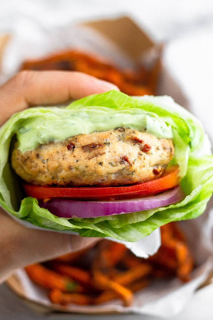 A hand holding a sun-dried tomato chicken burger wrapped with lettuce with a basket of sweet potato fries behind it.