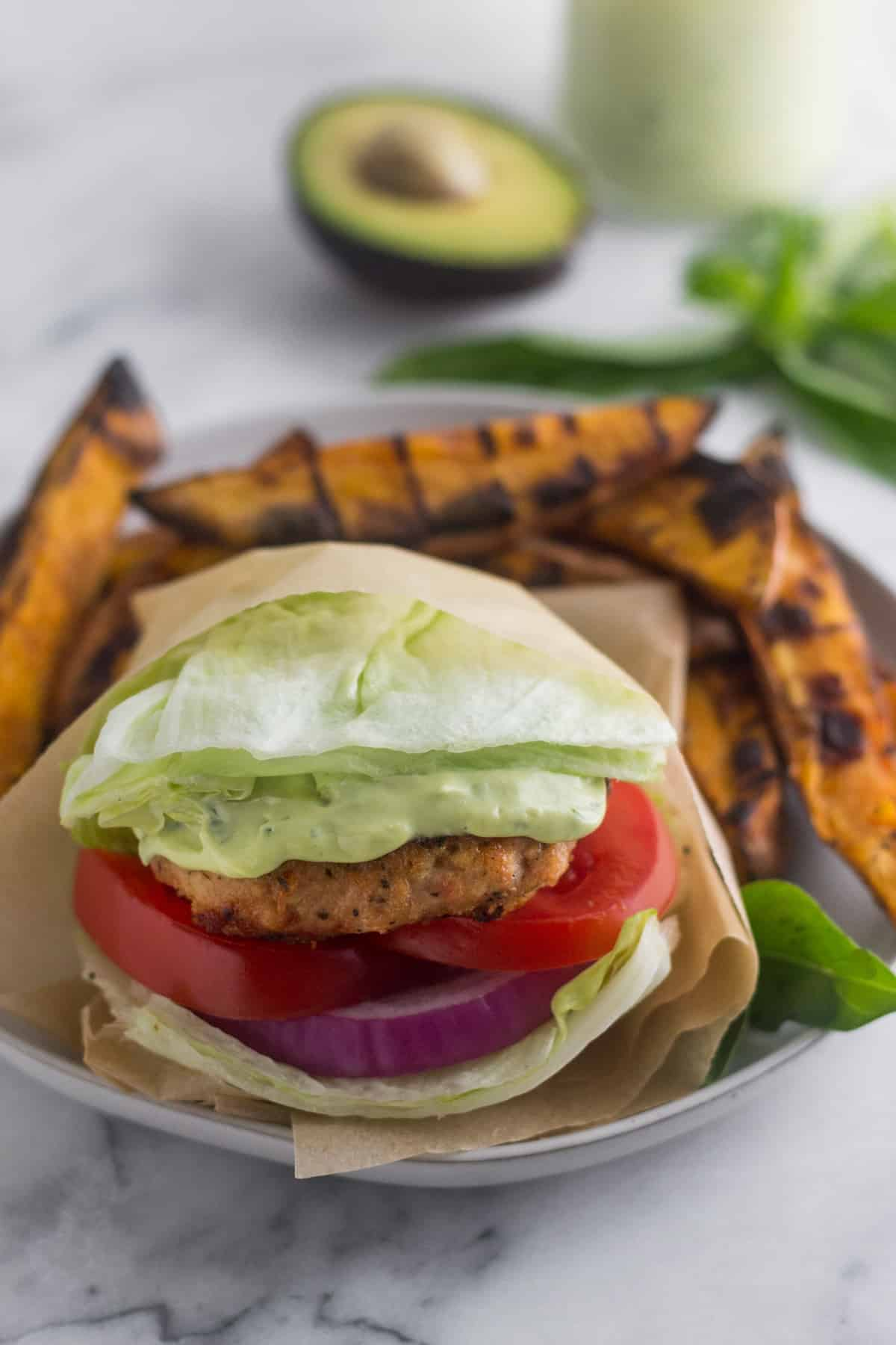 Sun dried tomato chicken burger wrapped in a lettuce wrap on a plate surrounded by grilled sweet potato fries