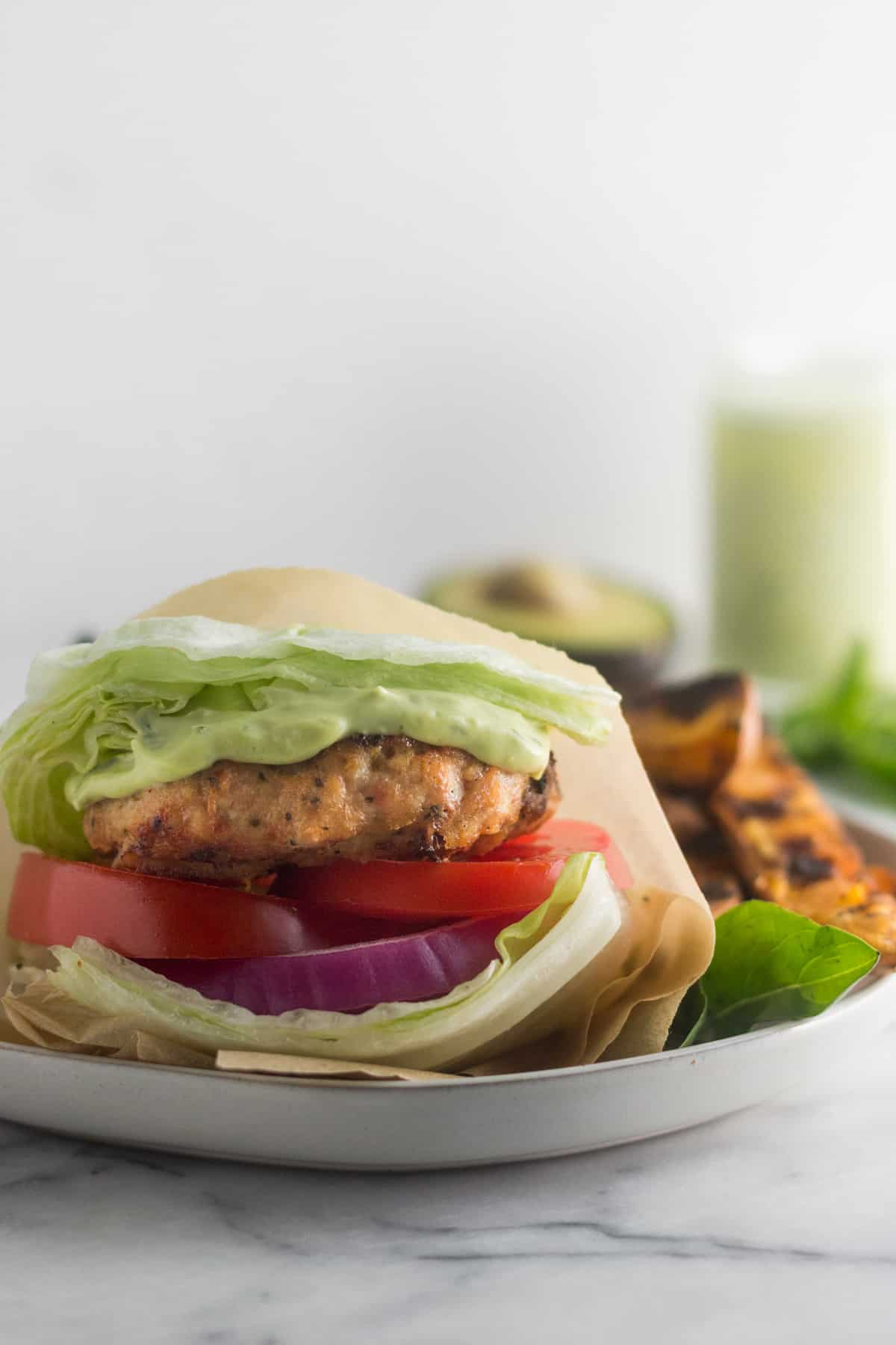 Sun dried tomato chicken burger wrapped in a lettuce wrap on a plate with sweet potato fries with an avocado basil aioli and an avocado behind it