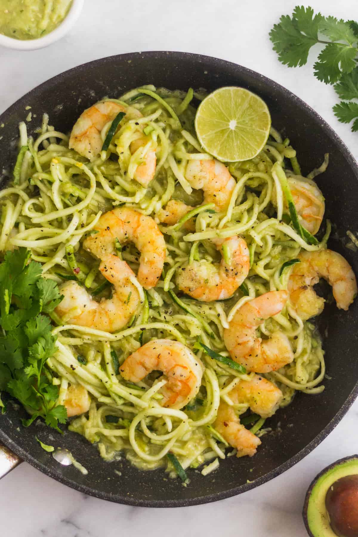 Large sauté pan filled Whole30 Tomatillo Salsa Shrimp Zucchini Noodles garnished with cilantro and lime