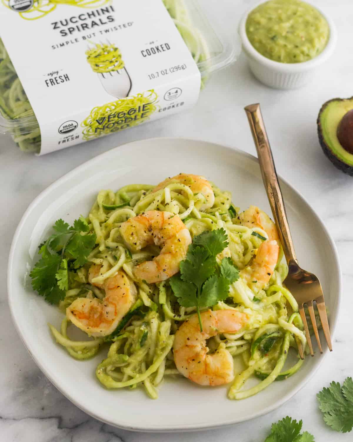 White plate with Whole30 Tomatillo Salsa Shrimp Zucchini Noodles with a box of zucchini noodles and a cup of tomatillo salsa behind it