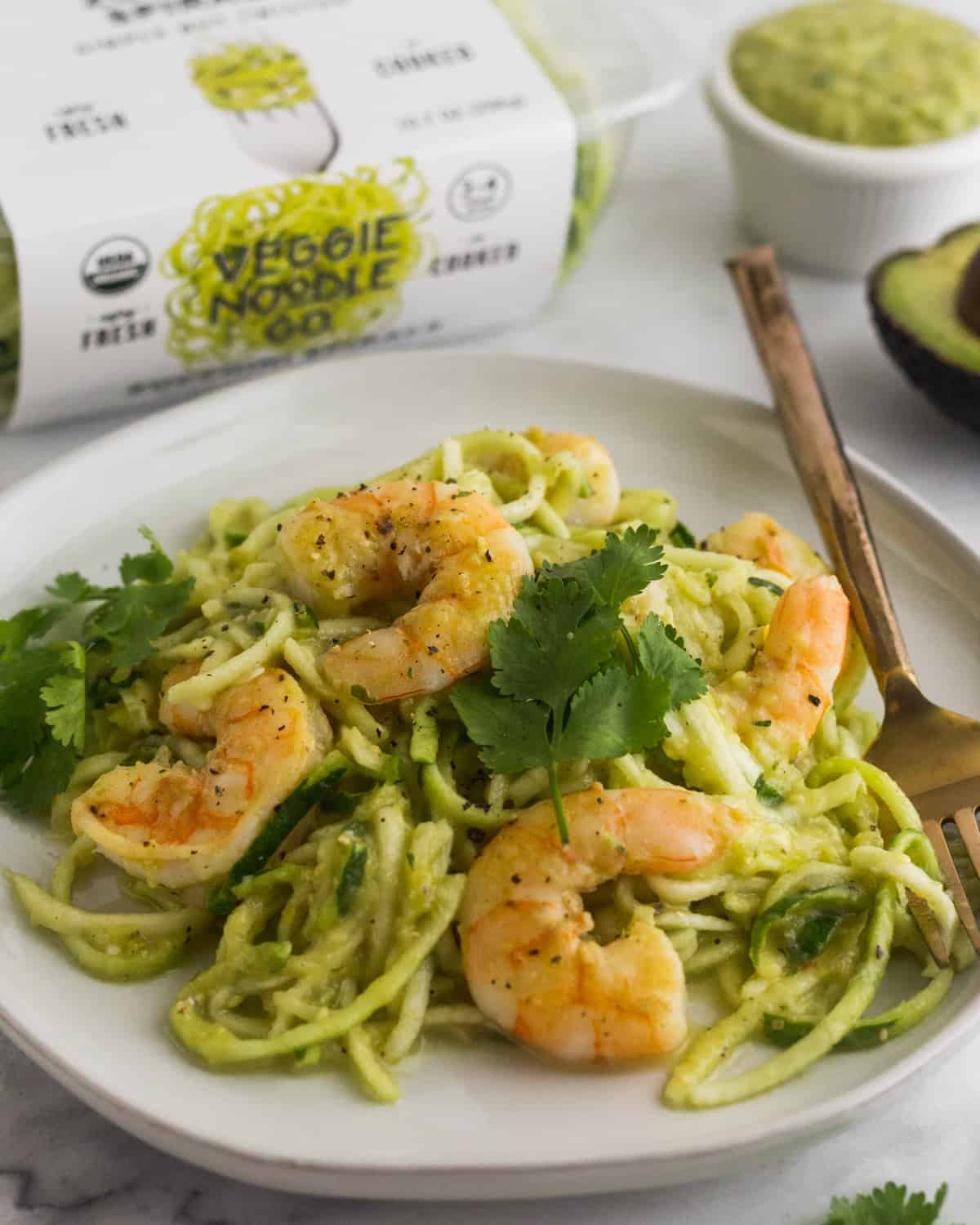 Plate of Whole30 Tomatillo Salsa Shrimp Zucchini Noodles with a fork in them and a box of zucchini noodles behind it