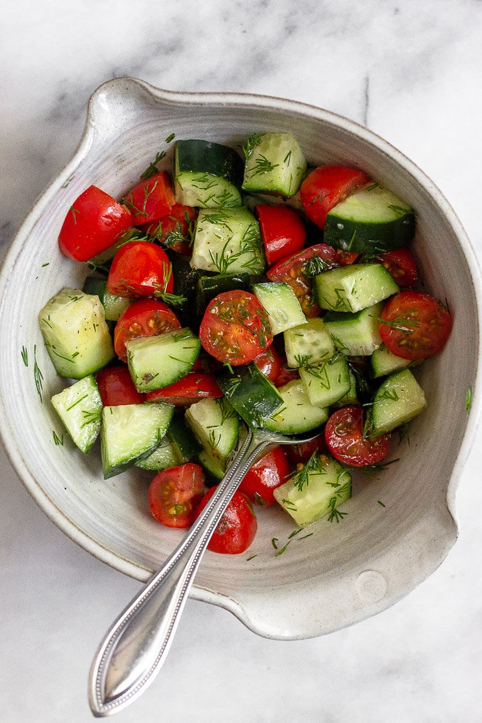 Bowl of diced cucumber and tomatoes with dill mixed in. There is a spoon sticking out of the bowl.