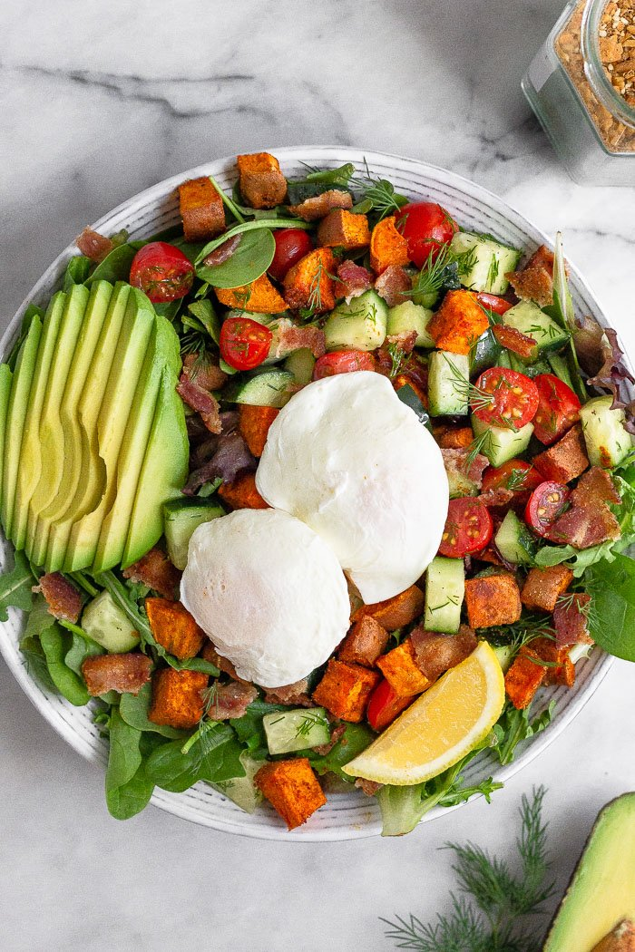 Avocado egg breakfast salad with two poached eggs on a large plate. Next to it is half an avocado and a jar of spice mix.