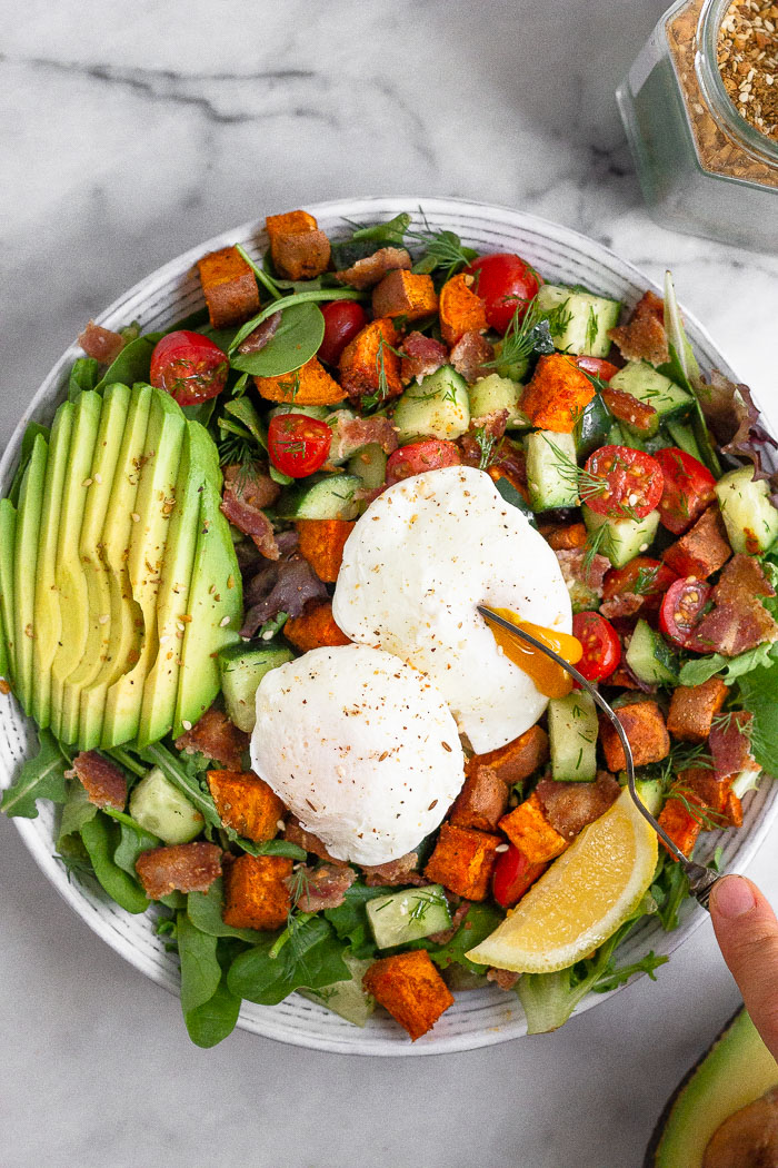 Overhead shot of a breakfast salad with poached eggs with a fork breaking open one of the eggs.