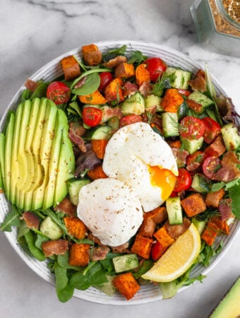 Overhead shot of a breakfast salad with veggies, sliced avocado, and two poached eggs with one of them cut open and the yolk is gushing out.