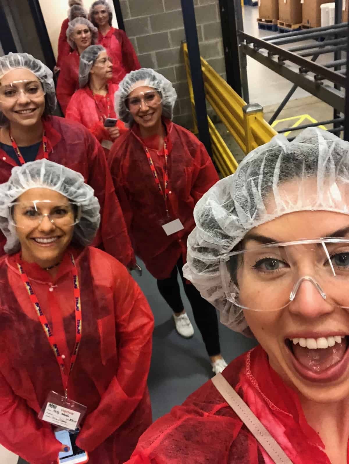 Group of girls inside the factory of a natural foods company in factory gear