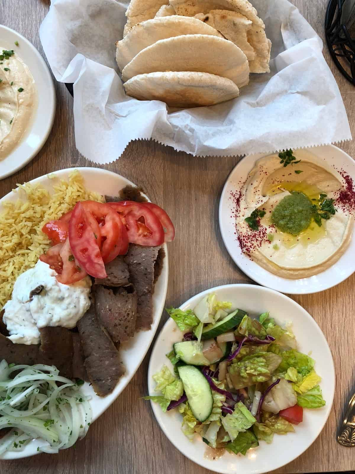 Big basket of pita, a gyro plate, plate of hummus, and a plate of greek salad at Middle Eastern Bakery and Grocery in Chicago, IL