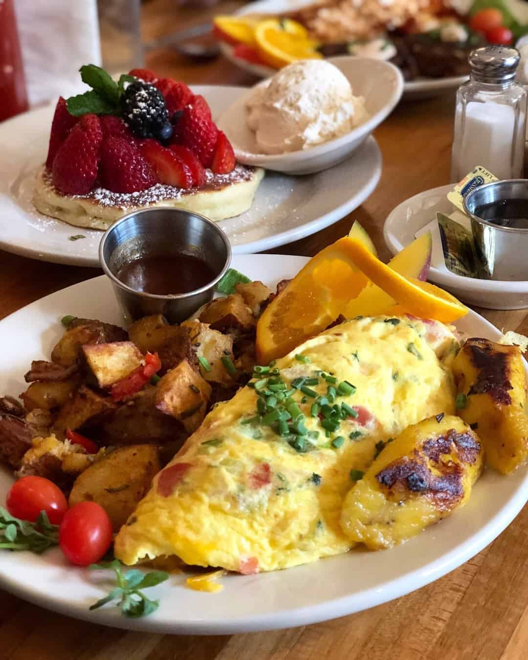 Loaded veggie omelet wit h a side of crispy potatoes and plantains with a pancake topped with berries and a side of whipped cream behind it
