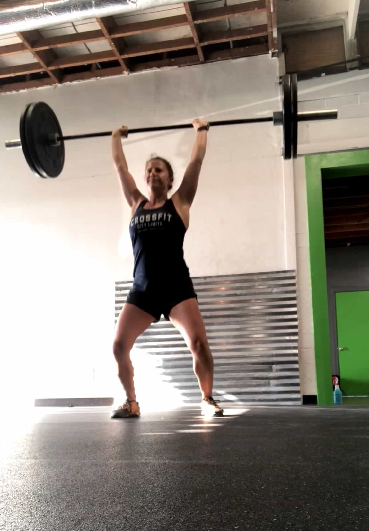 Girl doing a push jerk with the barbell over her head