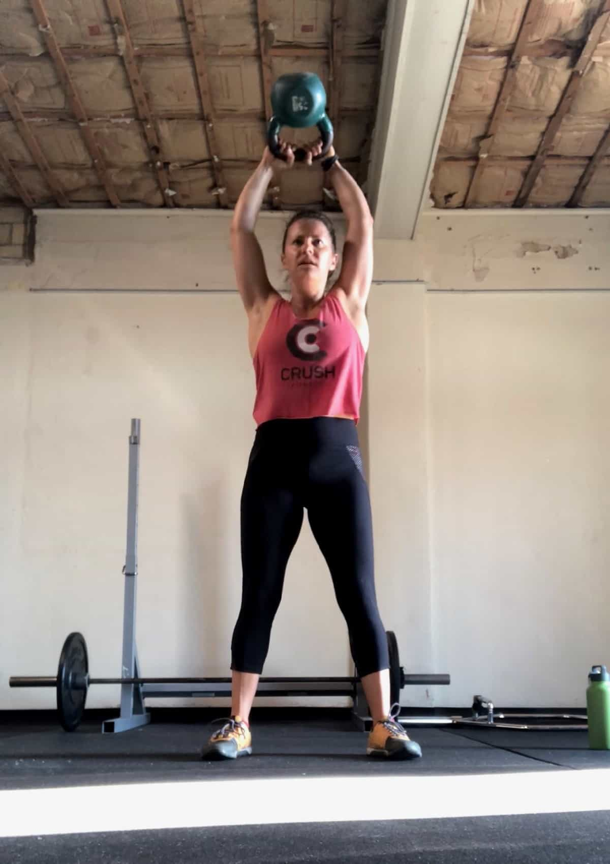 Girl doing a kettlebell swing with the kettlebell over her head