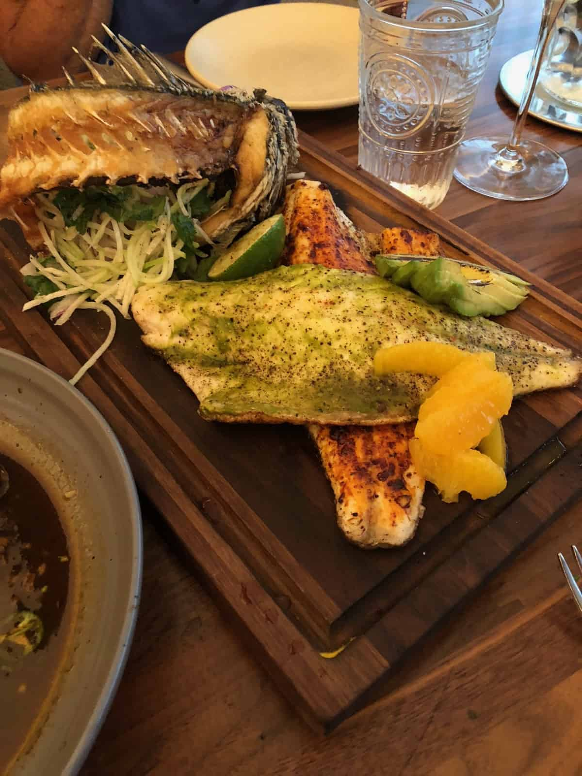 Cutting board with branzino two ways - one with a red sauce and one with a green sauce