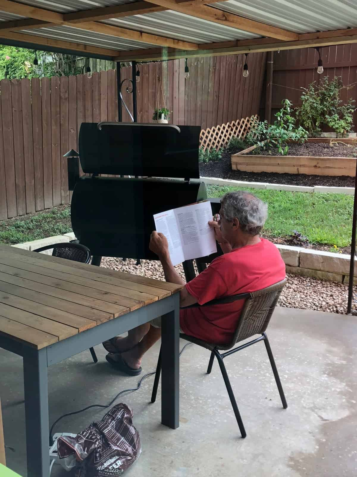 Man reading a manual for a Traeger grill with a Traeger grill behind him