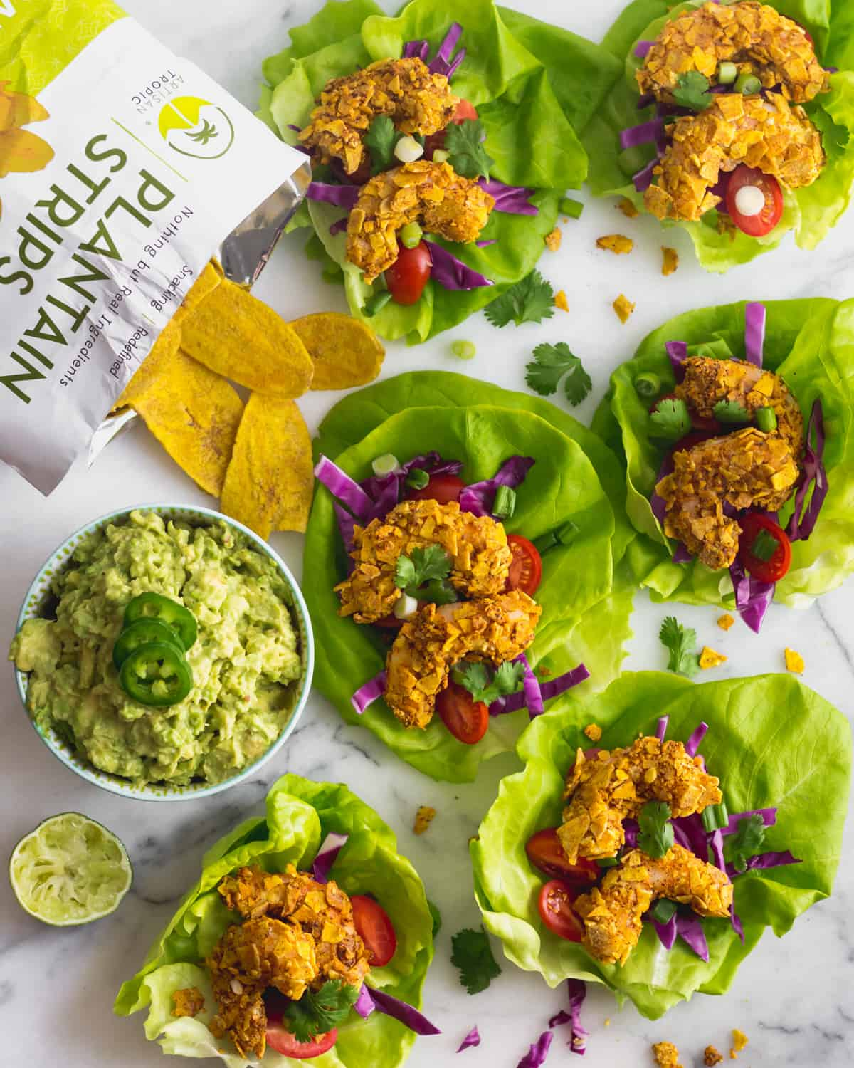 A bunch of Paleo Plantain Crusted Crispy Shrimp Tacos on a white counter with a bowl of guacamole and a bag of plantain chips around them