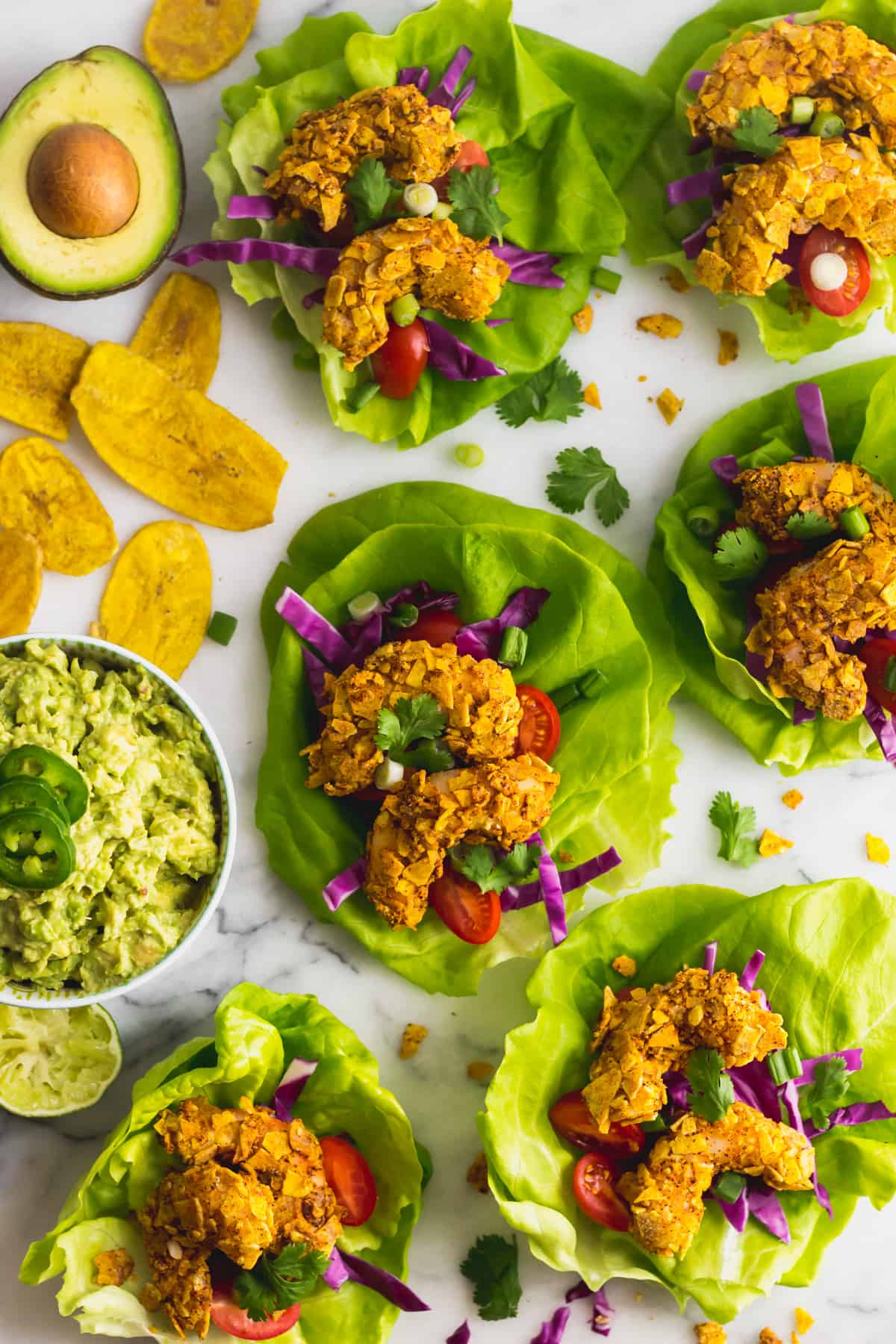 A bunch of Paleo Plantain Crusted Crispy Shrimp Tacos on a white counter with a bowl of guacamole and plantain chips around them