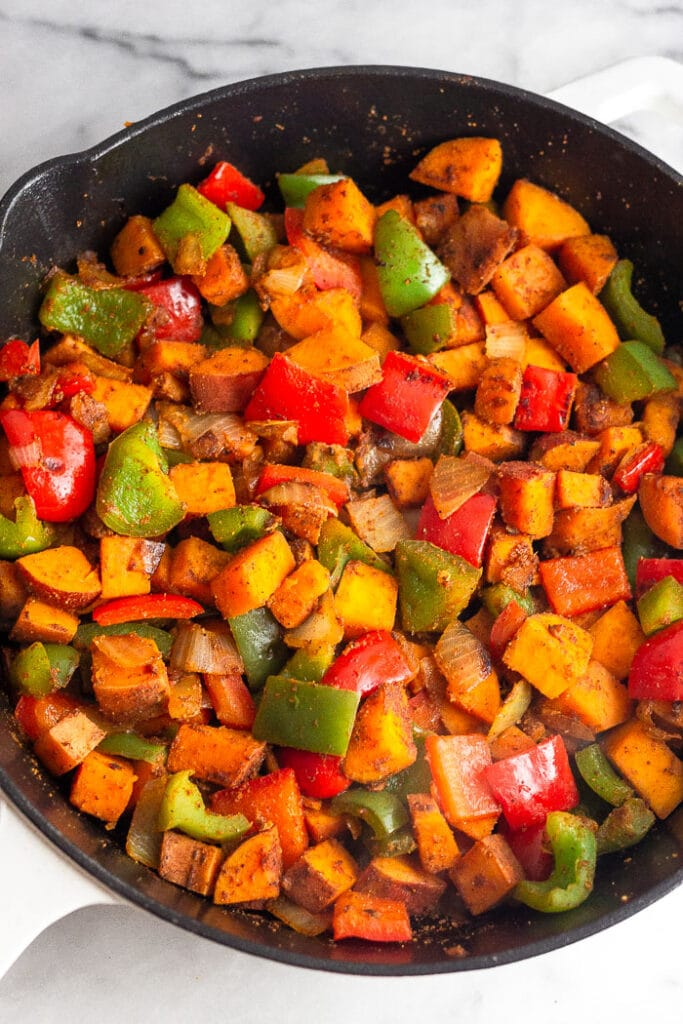 Large cast iron skillet filled with sautéed peppers, onions, and sweet potatoes.