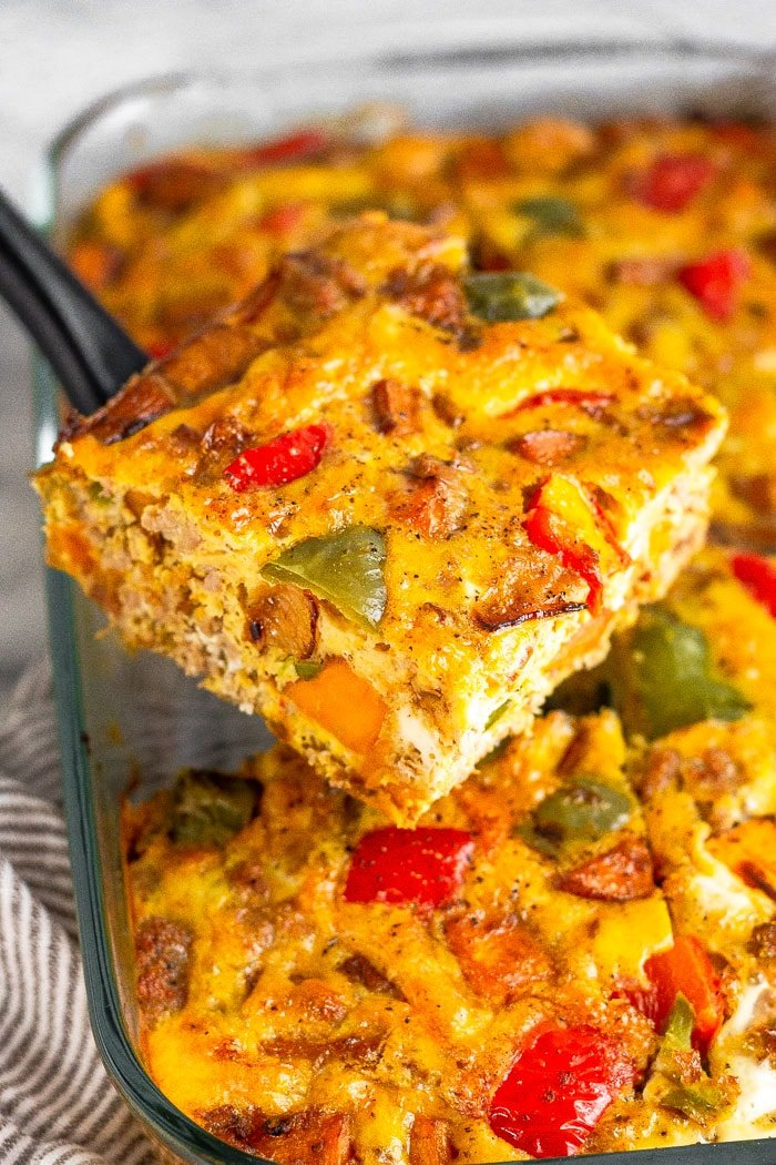 A piece of paleo breakfast casserole being held with a spatula over the plan of the rest of the casserole.