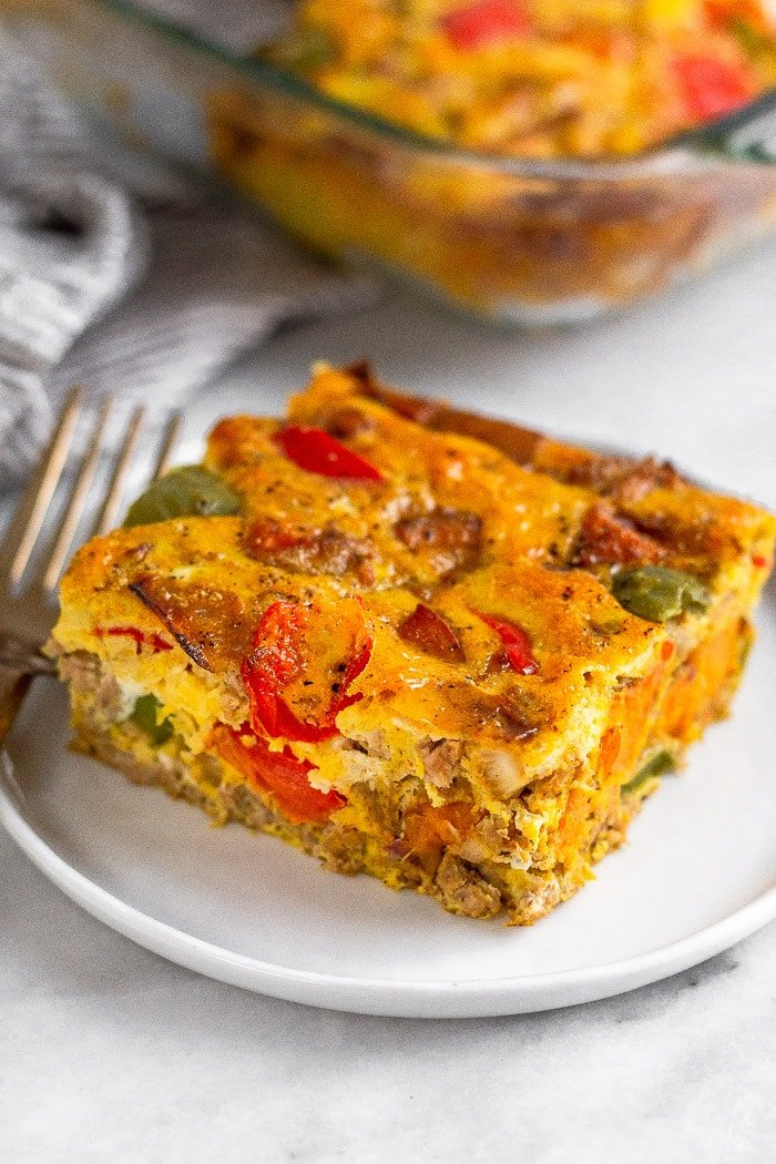 A piece of sausage sweet potato breakfast casserole on a plate with a fork next to it. Behind it is the whole casserole in a baking dish.
