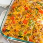 Large glass baking dish filled with Whole30 Sweet Potato and Sausage Casserole sitting on a white linen