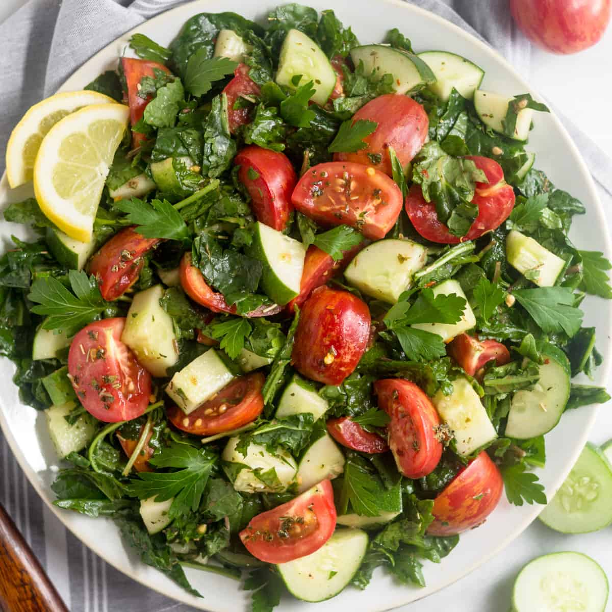 Large white plate filled with Chopped Tomato Cucumber Kale Salad surround by salad tongs, sliced cucumber, and tomatoes