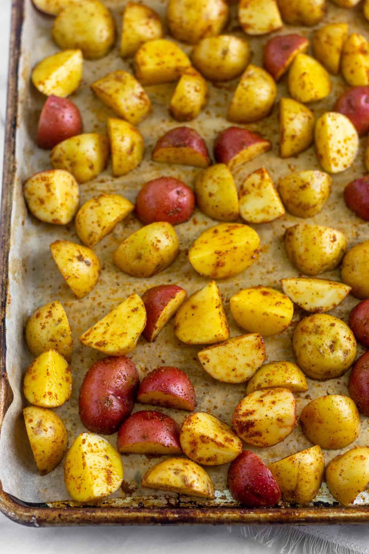 Baking sheet with quartered raw potatoes on it covered in spices waiting to be baked