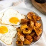 White plate with 2 fried eggs and crispy roasted breakfast potatoes with everyone sprinkled in pepper