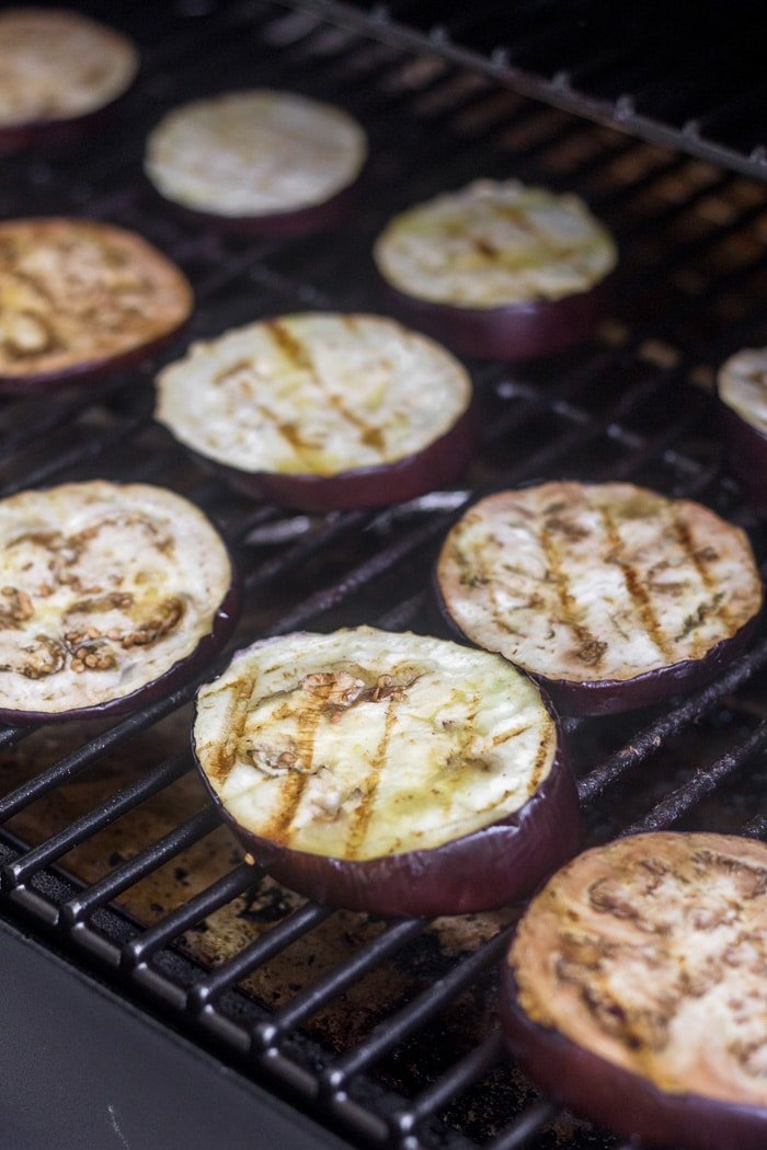 Grilled eggplant slices on the grates of a grill.
