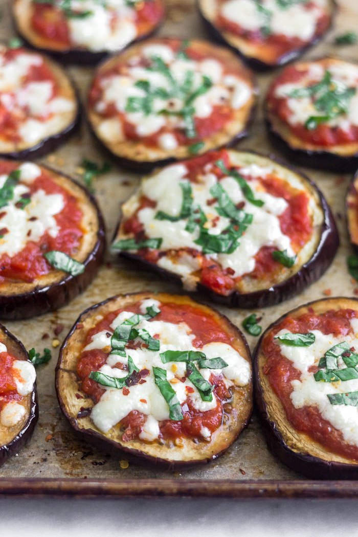 A bunch of eggplant pizza on baking sheet topped with basil and red pepper flakes.